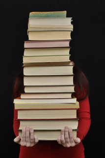 lady in red holding a stack of books ss